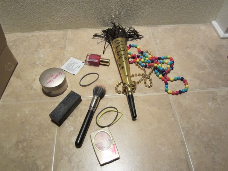 In this photo you see a random collection of stuff I included for my sissy: Makeup & old makeup brush (all used by me at some point in the past) - Nail polish (for his sissy fingernails!) - old hairbands, still with some stray hairs on them - New Years 2012 trumpet (used in videos by Domme Jayne and I!) - pride rainbow beads (included because I know my sissy loves to that I'm a lesbian)