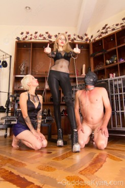 Now that my male gimp is out of the cage you can see the heavy metal chastity cage he wears when in my presence. You should also note the adoring look on subgirl Rexi's face while the gimp turns his face towards me wishing he could get a glimpse of my beauty.