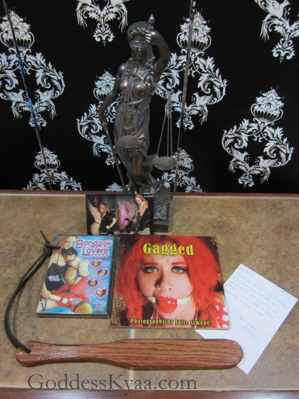 """""""Gagged"""" the book, a hot lesbian domination DVD featuring Julie Simone, RiotGirl stickers, a touching handwritten note and an amazing hardwood paddle."""